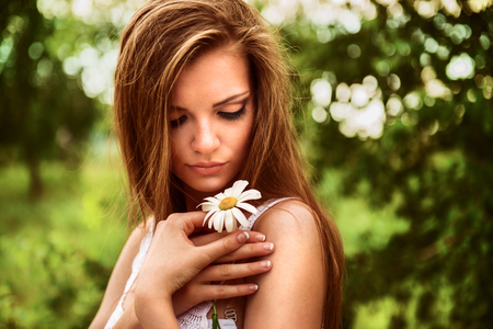 young beautiful woman outdoor in a birchwood with daisy flowers photo