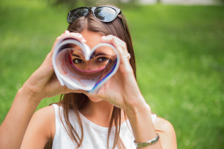 read magazine: A young brunette woman outdoors in a park looking through a heart shaped magazine