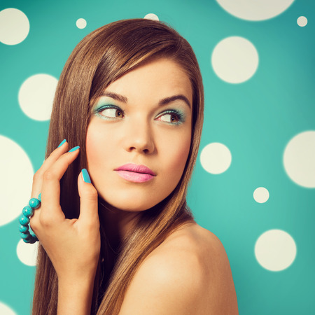 bright colour: Young beautiful woman holding a turquoise bracelet with bright colour manicure and makeup. Girl looking to the side. Vintage styled colors.