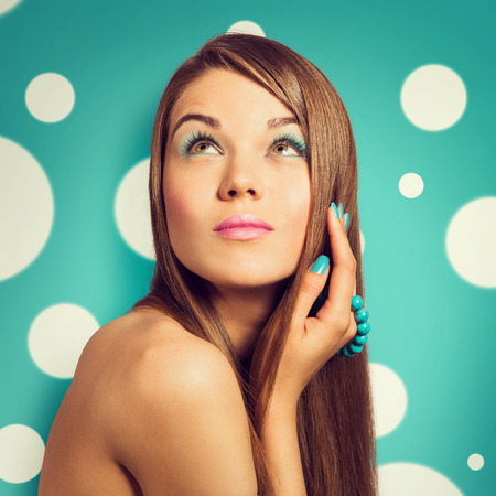 bright colour: Young beautiful woman holding a turquoise bracelet with bright colour manicure and makeup