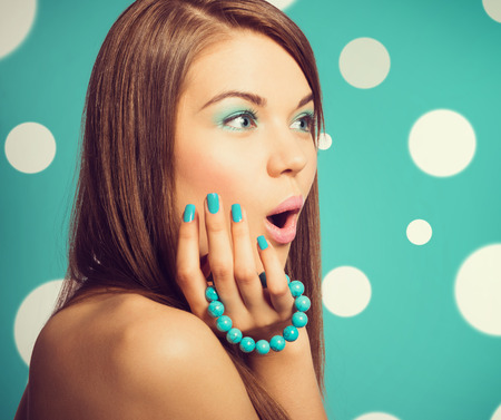 a bracelet: Young beautiful surprised woman holding a turquoise bracelet with bright colour manicure and makeup Stock Photo