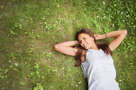 lazy: Young brunette woman enjoying the lying on her back on the green grass in the garden. Top view.
