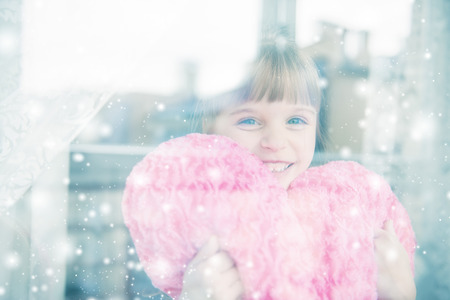Little girl behind a window. Its snowing outside.