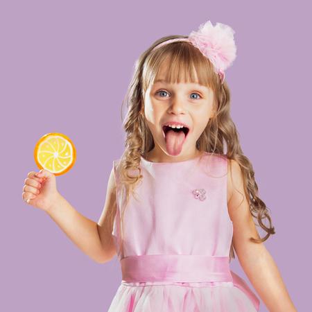 Kleines Mädchen posiert in einem Studio über Farbe Hintergrund. Hält eine orange Süßigkeiten. Standard-Bild - 33053058