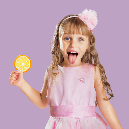 Little girl posing in a studio over colour background. Holding an orange candy.