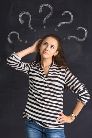 A shot of attractive young woman standing in front of a blackboard with a question sign photo
