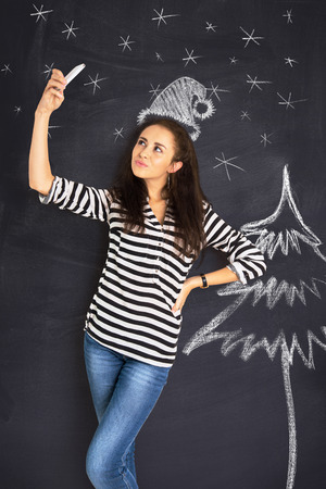 imagining: A shot of attractive young woman standing in front of a blackboard and making selfie. Imagining shes Santa Claus Stock Photo