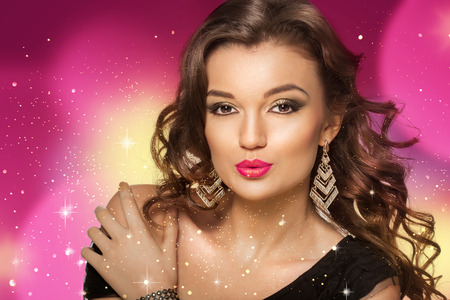 dishevel: Beauty shoot of smart brunette woman in motion over colored background and sparkles. Evening makeup and dark curly hairs.