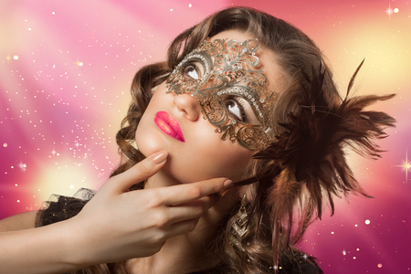 dishevel: Beauty shoot of smart brunette woman in carnival mask over colored background and sparkles. Evening makeup and dark curly hairs. Stock Photo
