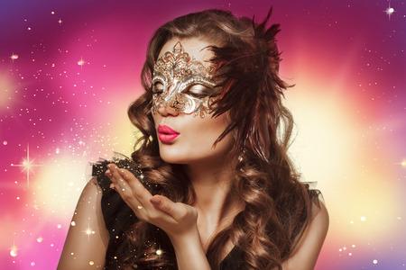 dishevel: Tiro di bellezza di donna bruna intelligente in maschera di carnevale su sfondo colorato e scintille. Trucco di sera e capelli ricci scuri.