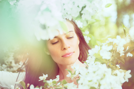 Portrait of spring brunette girl standing outdoor in blooming trees. Beautiful romantic woman in apple flowers. Young woman enjoying nature.