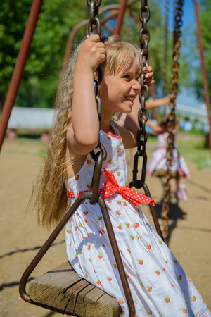 five years old: Happy little girl five years old wearing summer dress having fun on a swing in the park on a hot sunny summer day