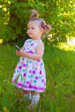 whimsy: Cute little girl wearing polka dots dress in a park on a summer sunny day holding mobile phone