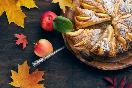 woden: Fresh baked apple pie on the woden table witn autumn leaves around Stock Photo