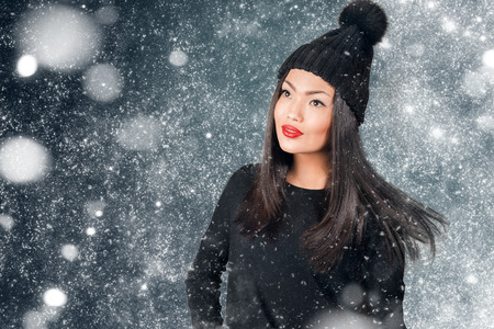 pompom: Beautiful asian woman wearing knitted hat with pompom in a snow. Stock Photo