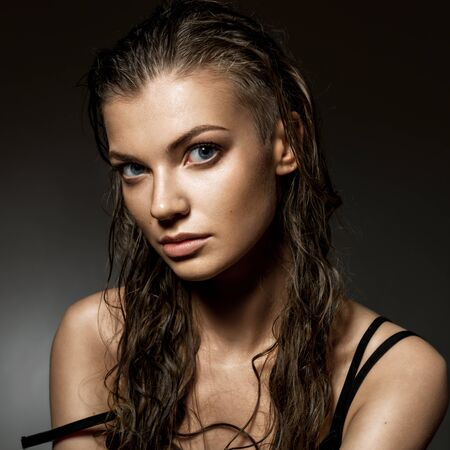 Portrait of beautiful young woman with long wet hairs. Low key studio shot.