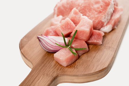 Fresh raw sliced pork meat is ready for preparation with rosemary and onion on wooden board.