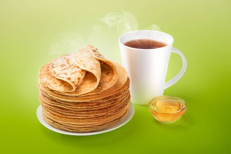 Stack of fresh baked pancakes with butter, honey and hot tea.