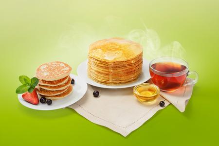 Stapel von frisch gebackenen Pfannkuchen mit Butter, Honig und heißem Tee. Standard-Bild - 54902774