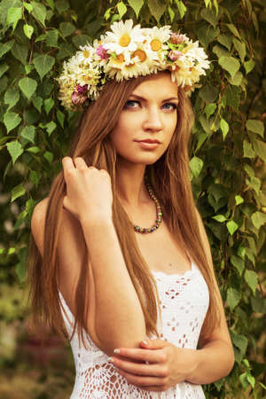 young beautiful woman outdoor in a birchwood wearing wreth of daisy flowers
