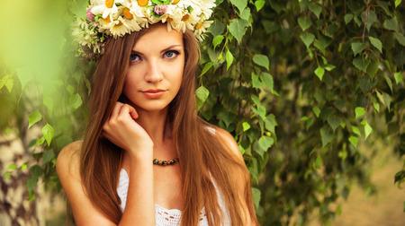 birchwood: young beautiful woman outdoor in a birchwood wearing wreth of daisy flowers