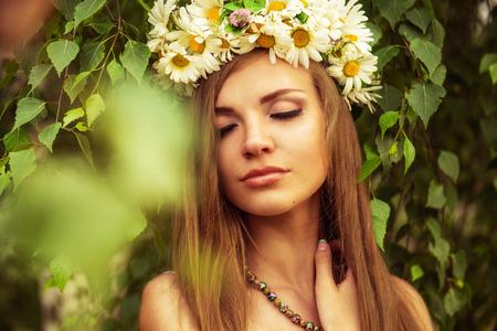 Junge schöne Frau im Freien in einem Birkenholzxylan wreth von Daisy Blumen tragen Standard-Bild - 58529547