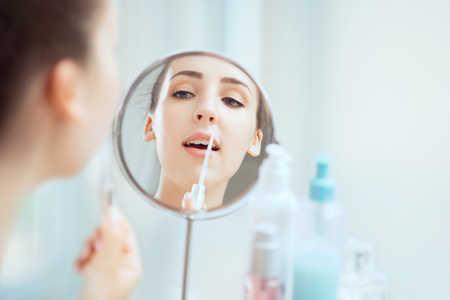 A reflection of a young brunette woman putting on a lipgloss looking in the round mirror.