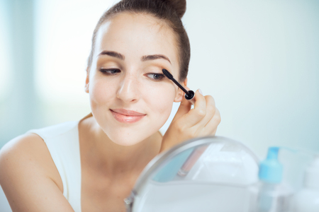 miror: A young brunette woman putting on mascara, looking in the round mirror