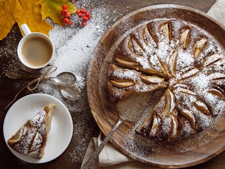 Frisch gebackener Apfelkuchen auf der wodden Tabelle mit Herbstlaub um Standard-Bild - 63947139