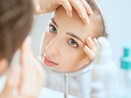 Shot of a reflection of a young woman examining her face in the round mirror