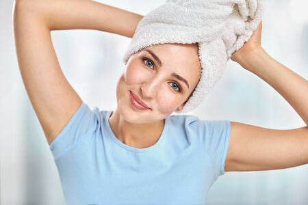fair complexion: A young brunette woman with a towel wrapped round her head holding the towel by her hands
