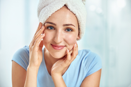 fair complexion: A young brunette woman with a towel wrapped round her head touching her cheeks by her both hands