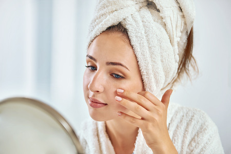 A young brunette woman with a towel wrapped round her head  examining her face in the round mirror Stock Photo