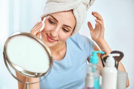 Eine junge Frau mit einem Handtuch eingewickelt um ihren Kopf, um ihre Haut mit einem Wattebausch Reinigung Standard-Bild - 67827476