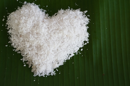 love sign from grated coconut on banana leave photo