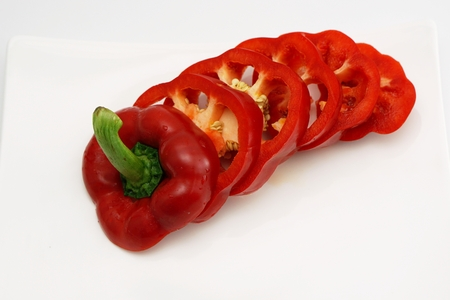 slightly: isolated red slightly cut sweet pepper on dish