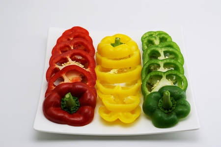 slightly: isolated set of slightly cut sweet pepper on dish Stock Photo