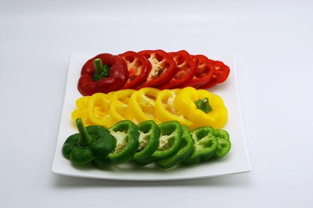 slightly: isolated set of slightly cut sweet pepper on dish Stock Photo