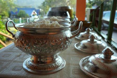 limosna: llena de ofrendas de arroz en un taz�n de limosnas de un monje budista
