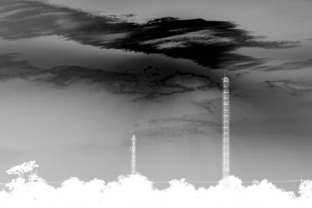 transmitter: abstract black and white phone transmitter towers with dark sky Stock Photo
