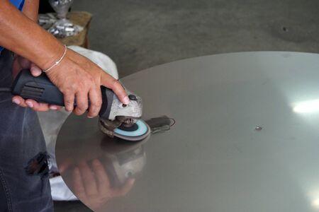 worker is used grinding machine grind on the metal plate