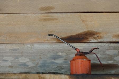 oiler: old oiler on the wood shelf in garage Stock Photo