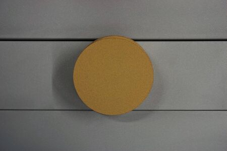 aluminum background: yellow round sand paper for metal grinding with aluminum background