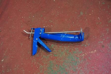 caulk: broken of blue silicone caulking gun on floor in the factory Stock Photo