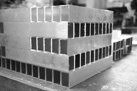 shiny black: stack of aluminum square tube in the factory