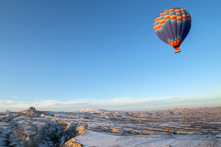 adventure holiday: Hot air balloons fly over Cappadocia in winter, Goreme, Turkey.