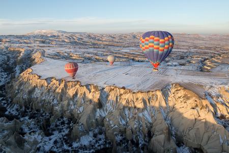 Hot air balloons fly over Cappadocia in winter, Goreme, Turkey.