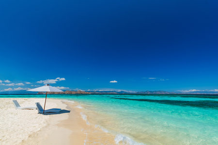 Beautiful beach. Sunbeds with umbrella on the sandy beach near the sea. Summer holiday and vacation concept. Inspirational tropical beach.