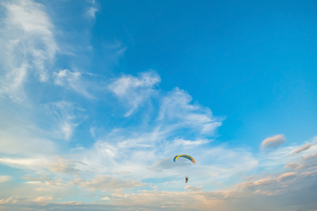 A flying paramotor on a vibrant sky with cloud. Extreme sport.