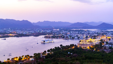 Udaipur city at lake Pichola in the evening, Rajasthan, India. View from  the mountain viewpoint see the whole city reflected on the lake.